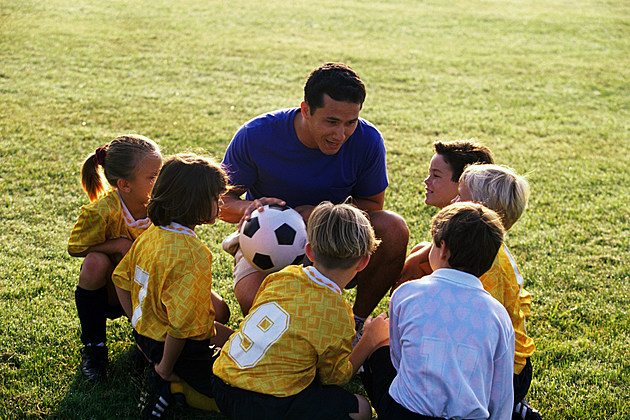 football coach giving advice to young football team