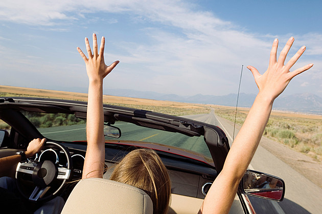 Woman in convertible with arms raised